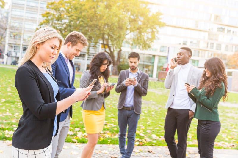 Utomhus- grupp människor se deras egna smarta telefoner royaltyfria foton