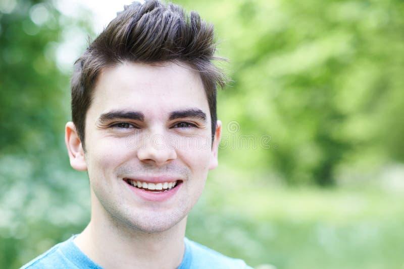 Utomhus- Head och skuldrastående av att le den unga mannen fotografering för bildbyråer