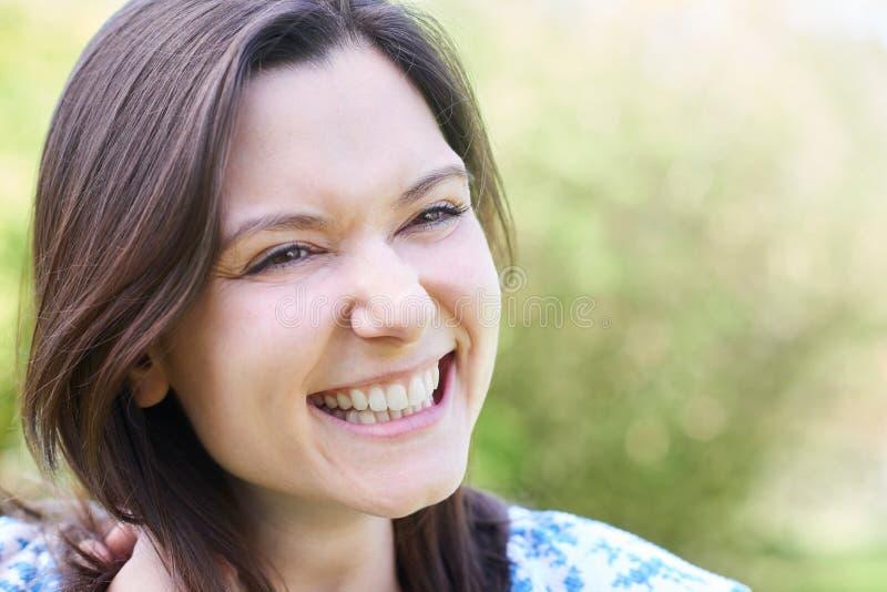 Utomhus- Head och skuldrastående av att skratta den unga kvinnan royaltyfri bild