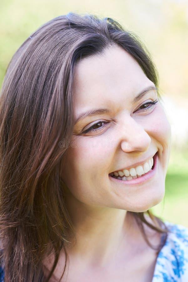 Utomhus- Head och skuldrastående av att skratta den unga kvinnan royaltyfri fotografi