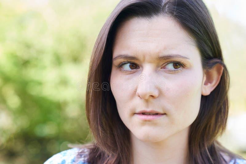 Utomhus- Head och skuldrastående av den bekymrade unga kvinnan arkivbild