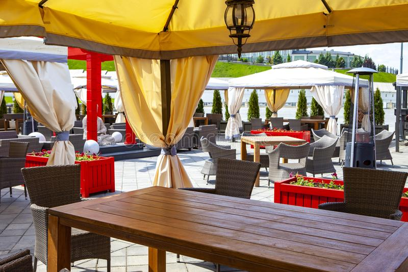 Utomhus- kafé med en traditionell stil med tabeller, stolar, blommor, lampor och en Buddhastaty royaltyfri bild