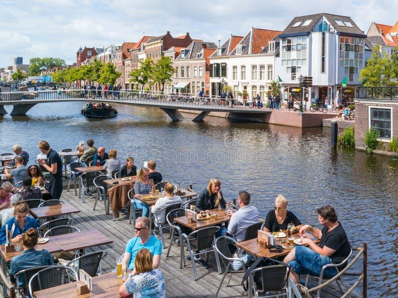 Utomhus- kafé och bro över Rhenkanalen, Leiden, Nederländerna royaltyfria foton