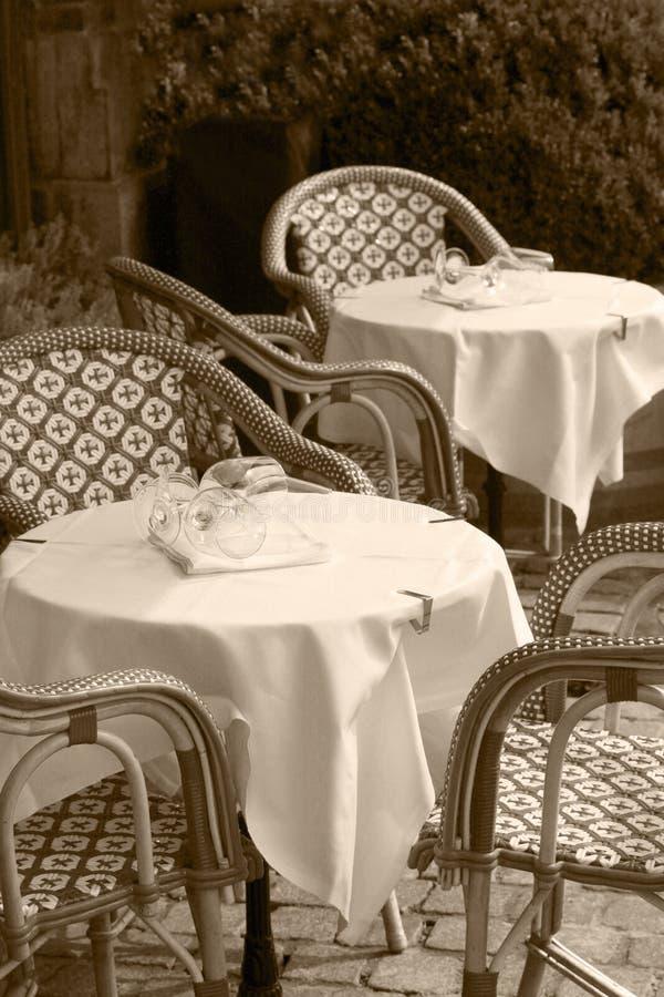 Utomhus- kafé och restaurang med tabeller, stolar och exponeringsglas som väntar på kunder att ankomma i svartvit sepiasignal royaltyfri bild