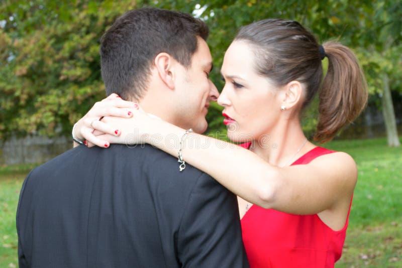 utomhus- kysskramstående av unga härliga flörta par royaltyfri fotografi