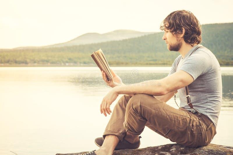Utomhus- läsebok för ung man fotografering för bildbyråer