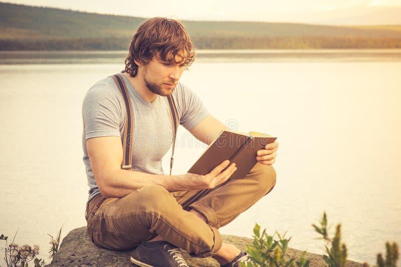 Utomhus- läsebok för ung man arkivfoto