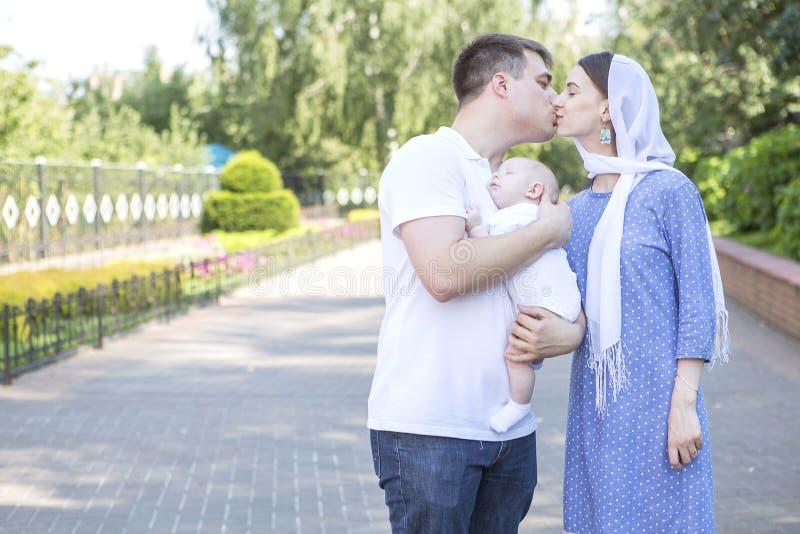 Utomhus- le för lycklig europeisk familj Deras mamma och farsa som rymmer royaltyfri bild