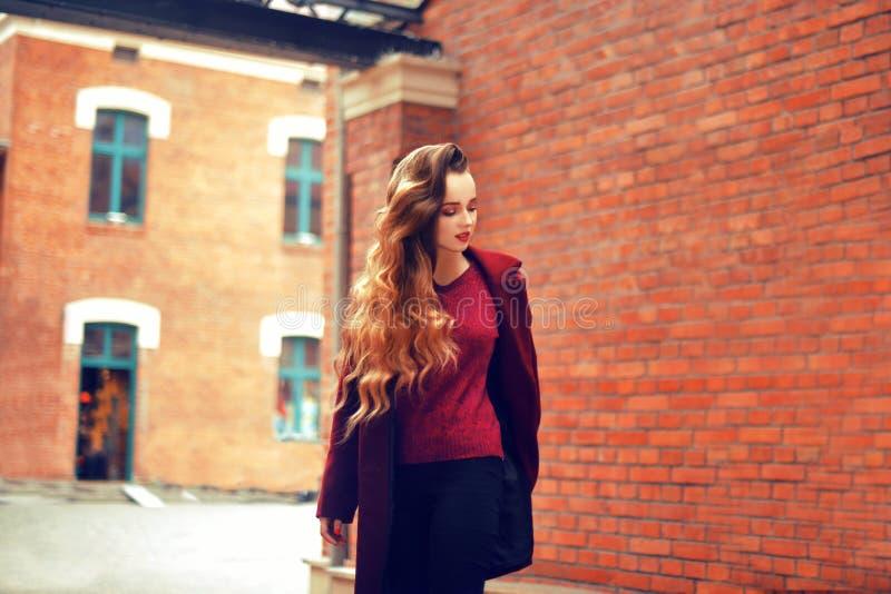 Utomhus livsstilmodestående av brunettflickan Bärande stilfullt rött lag Gå till stadsgatan Långt lockigt ljust hår royaltyfri foto