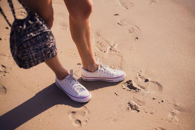Utomhus- livsstilnärbild av benen av den härliga tonårs- flickan Ungt hipsterkvinnaband snör åt i hennes vita gymnastikskor royaltyfria foton