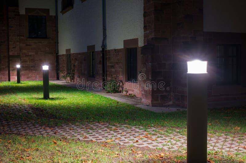 Utomhus- ljus framme av en gammal byggnad som exponerar en gångbana i trädgården på natten royaltyfri fotografi