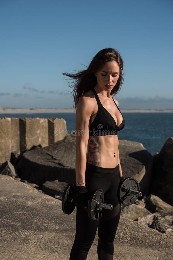 Utomhus- lyftande vikter för färdig kvinna - arkivfoto