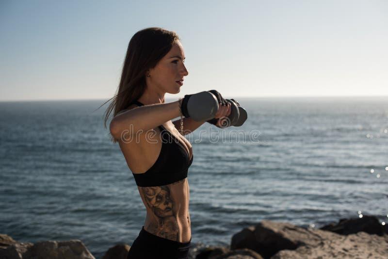 Utomhus- lyftande vikter för färdig kvinna - royaltyfri bild