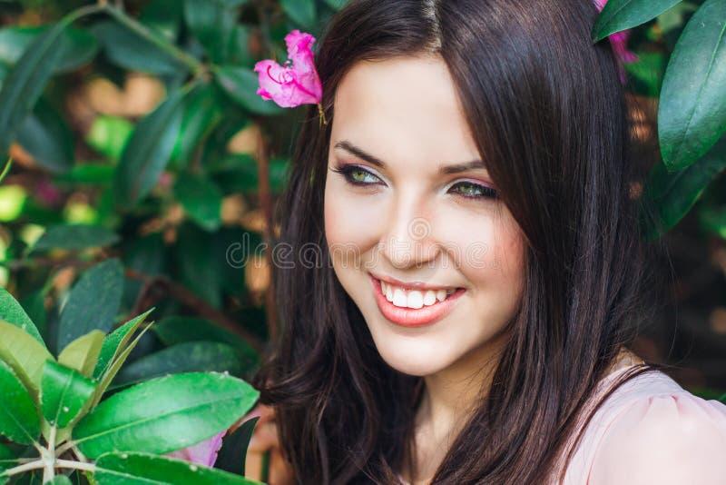 Utomhus- modefoto av den härliga unga kvinnan som omges av blommor fjäder för blomma för dof för azaleablomningclose grund upp arkivbilder