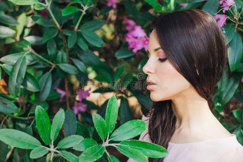 Utomhus- modefoto av den härliga unga kvinnan som omges av blommor fjäder för blomma för dof för azaleablomningclose grund upp royaltyfria foton