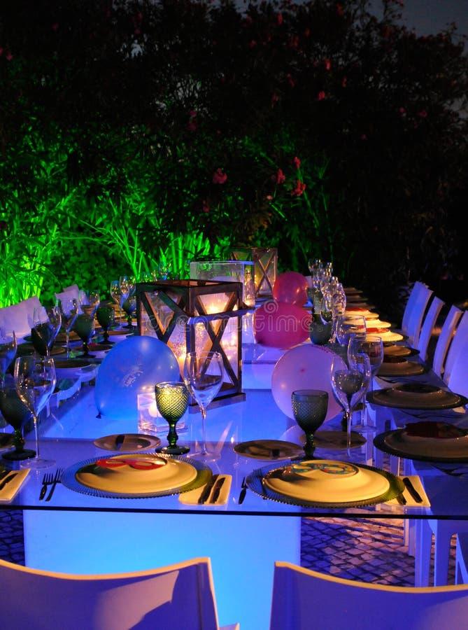 Utomhus- modern restaurang som tänds stearinljus och tabeller, vita servetter, rolig tabelluppsättning royaltyfri foto