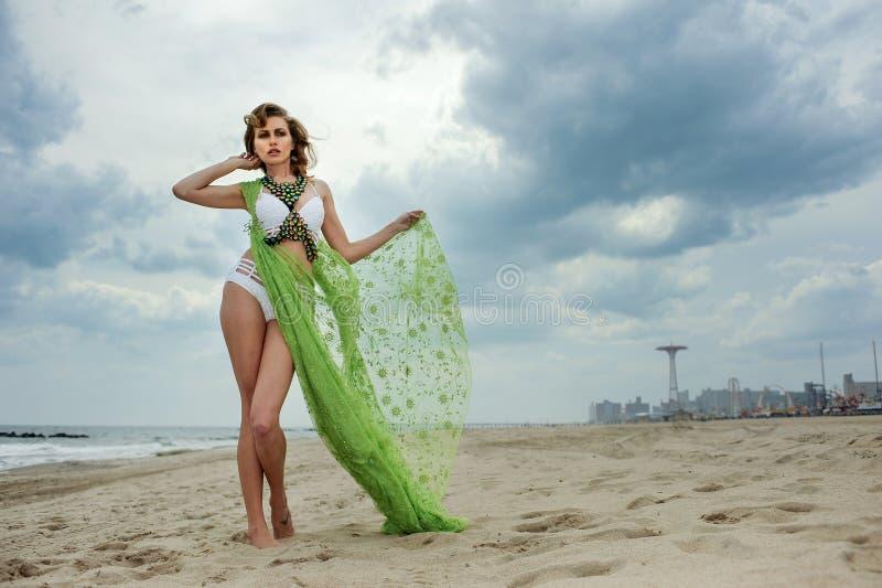 Utomhus- modesommarfoto av den härliga slanka kvinnan med den perfekta kroppen i lyxig designbikini royaltyfri foto