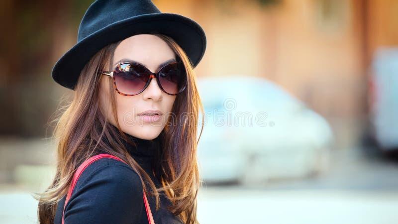 Utomhus- modestående av att le den unga kvinnan som bär den moderiktiga svarta hatten och stor retro solglasögon arkivbilder