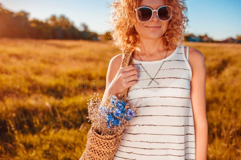 Utomhus- modestående av den härliga unga kvinnan med den röda innehavpåsen för lockigt hår med blommor Sommardräkt arkivfoto