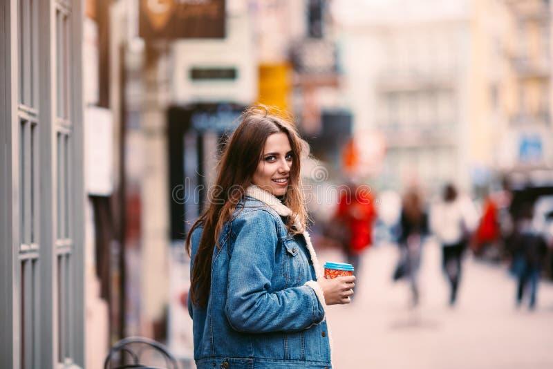 Utomhus- modestående av den stilfulla unga kvinnan som har gyckel, emotionell framsida, skratta som ser kameran Stads- stadsgatas arkivfoto