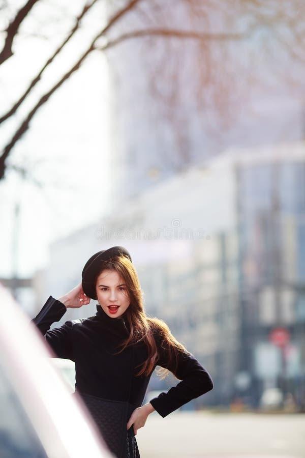 Utomhus- modestående av den stilfulla unga kvinnan som har gyckel, emotionell framsida, skratta som ser kameran Stads- stadsgatas royaltyfria bilder