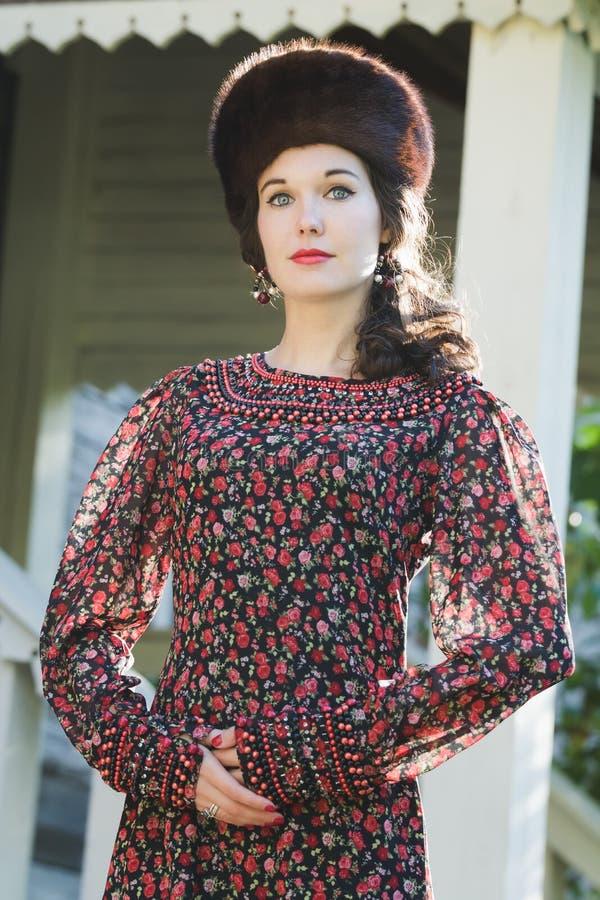Utomhus- modestående av den unga kvinnan i ryska medeltida stilkläder med pälskosackhatten arkivbilder