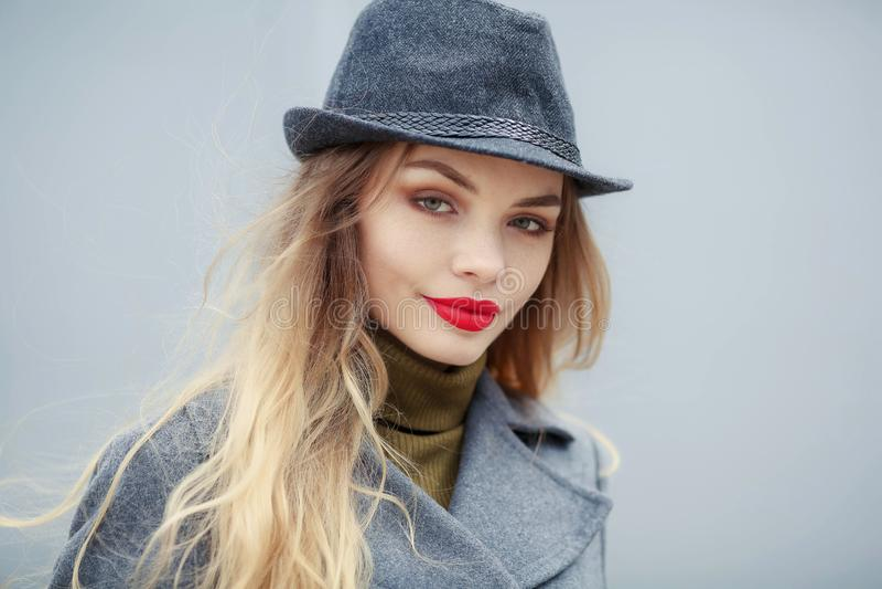 Utomhus- modest?ende av den unga h?rliga trendiga kvinnan som b?r stilfull tillbeh?r tappninghatt som ser kameran royaltyfri bild