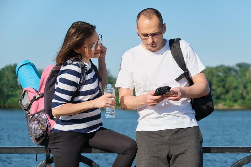Utomhus- mogna par genom att använda talande gå för smartphone, för man och för kvinna i parkerar arkivbild
