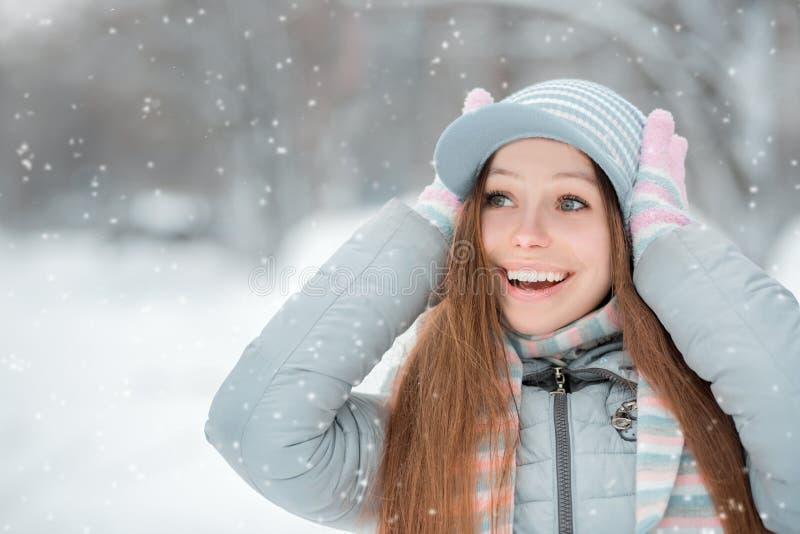 Utomhus- närbildstående av den unga härliga lyckliga le flickan, den bärande stilfulla stack vinterhatten och handskar Modell som royaltyfria foton