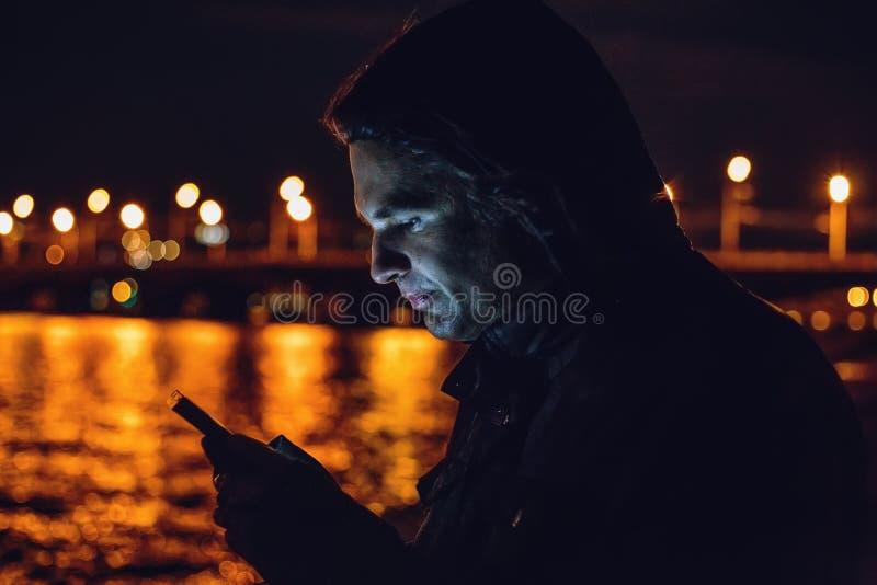 Utomhus- nattstående av den unga mannen som använder mobiltelefonen arkivfoton