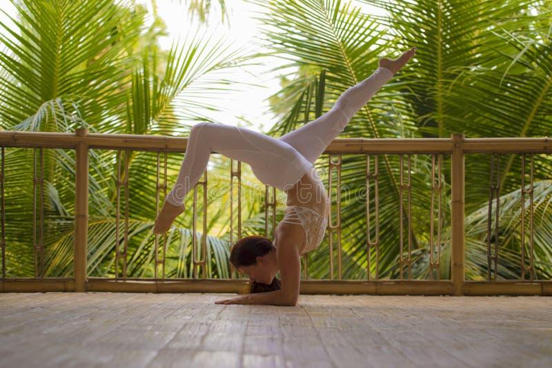 Utomhus naturlig stående av den unga härliga och lyckliga röda hårkvinnan som gör yoga på övande jämvikt för tropisk konditionstu arkivbild