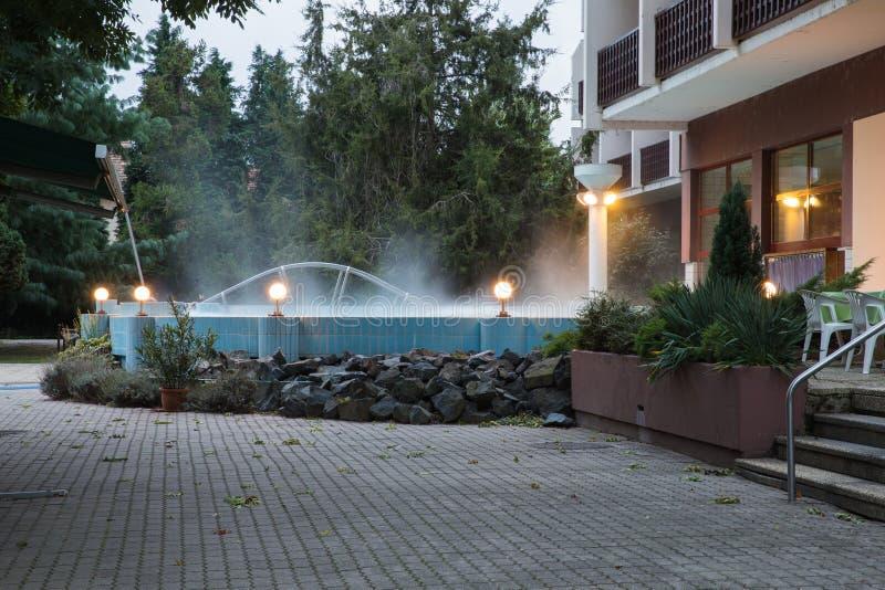 Utomhus- pöl med den termiska vattenbrunnsorten nära hotellet Vatten röker över pölen Termiskt komplex arkivbild