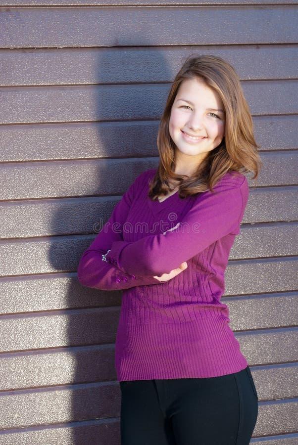 Ståenden av lyckligt le för härlig ung teen brunettflicka med räcker korsat fotografering för bildbyråer