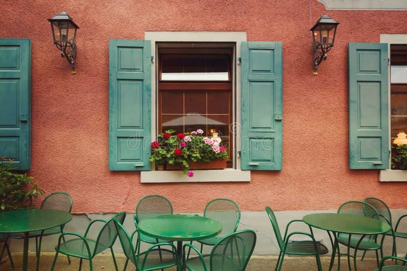 Utomhus- restaurangtabeller över byggnadsväggbakgrund Stads- detalj för gammal europeisk stad retro filter arkivfoton