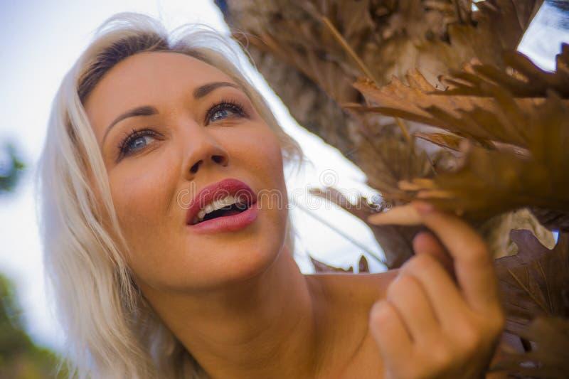Utomhus romantisk stående av det avkopplade unga attraktiva och härliga blonda bladet för kvinnainnehavträd och lyckligt le som ä arkivfoto