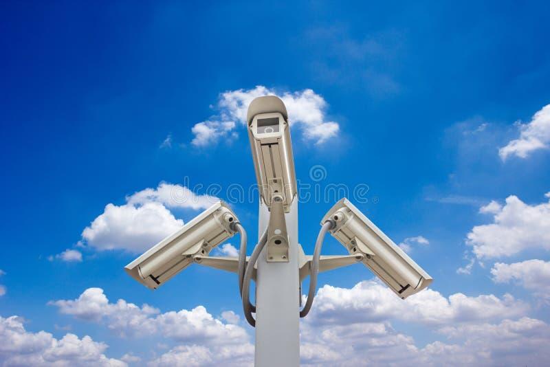 Utomhus- säkerhetscctv-kameror mot blå himmel och molnet arkivbild