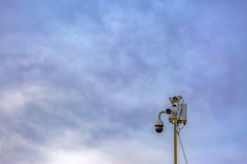 Utomhus- säkerhetskamera som isoleras mot en molnig bakgrund för blå himmel royaltyfri bild