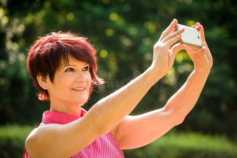 Utomhus- selfie för hög kvinna royaltyfri bild