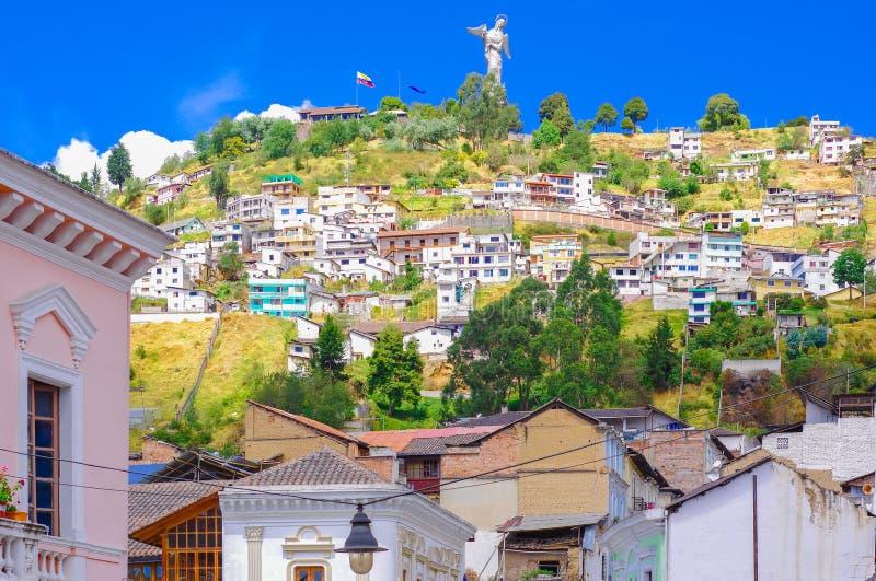 Utomhus- sikt av koloniala byggnadshus som lokaliseras i staden av Quito med statyn av oskulden av Panecillo i royaltyfria bilder