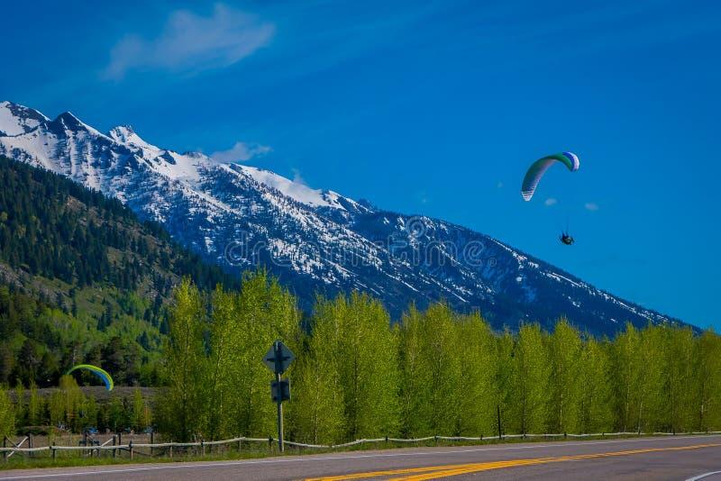 Utomhus- sikt av praktiserande paragliding för folk i storslagna Tetons på morgonljus med ett partiskt dolt för enorma berg royaltyfri foto
