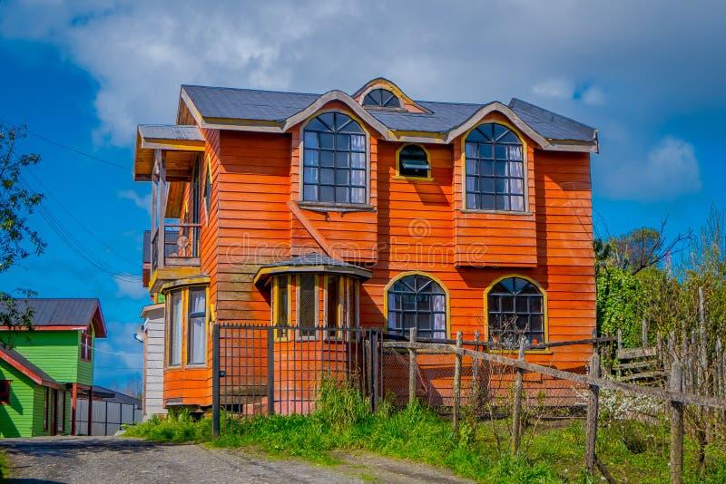 Utomhus- sikt av träorange byggnad i den Chiloe ön i en ursnygg blå himmel i Chile arkivfoto