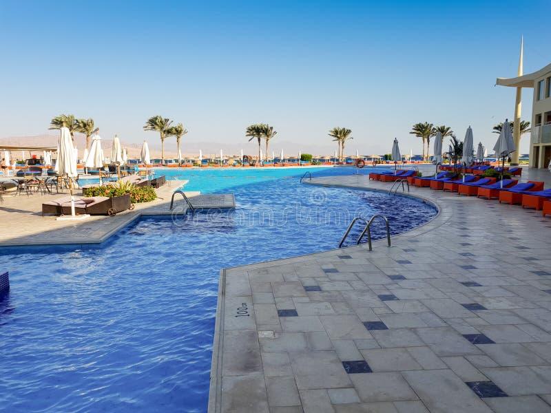 Utomhus- simbassäng med massor av solsängar på semesterorten för sommarstrandhotell royaltyfri bild