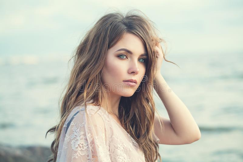 Utomhus- sinnlig kvinna Härlig modellflicka med långt lockigt brunt hår på havbakgrund arkivfoto