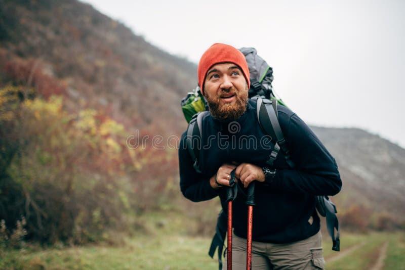 Utomhus- skott av den unga mannen för stilig Caucasian fotvandrare som fotvandrar i berg med loppryggsäcken royaltyfria foton