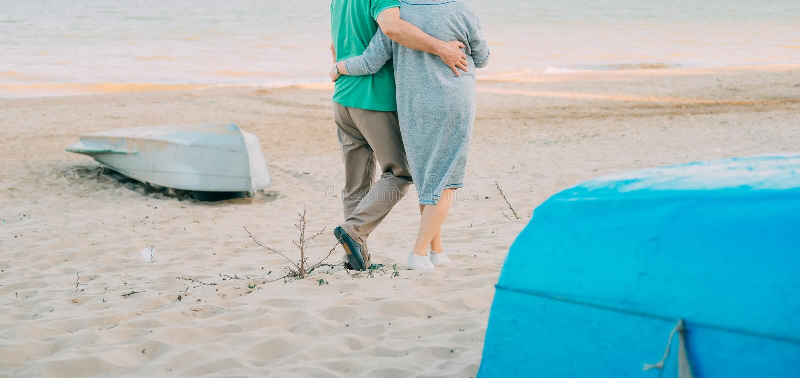 Utomhus- skott av romantiska höga par som promenerar händerna för innehav för havskust Hög man och kvinna som går på strandtogeth royaltyfri foto