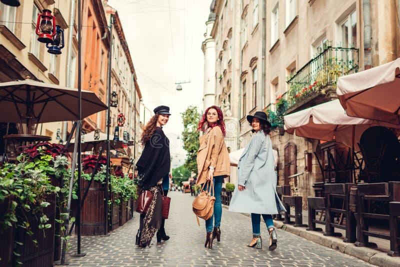 Utomhus- skott av tre unga kvinnor som går på stadsgatan Flickor som vänder och ser kameran royaltyfria bilder