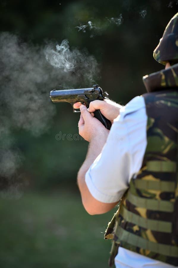 Utomhus- skytte med en 9mm pistol i en skjutbana arkivfoton