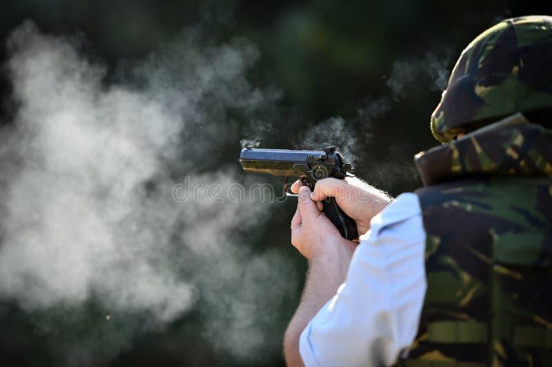 Utomhus- skytte med en 9mm pistol i en skjutbana arkivfoto