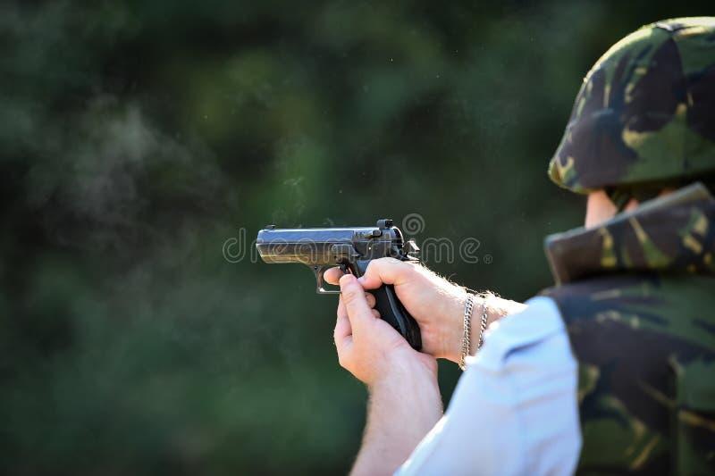 Utomhus- skytte med en 9mm pistol i en skjutbana arkivbild