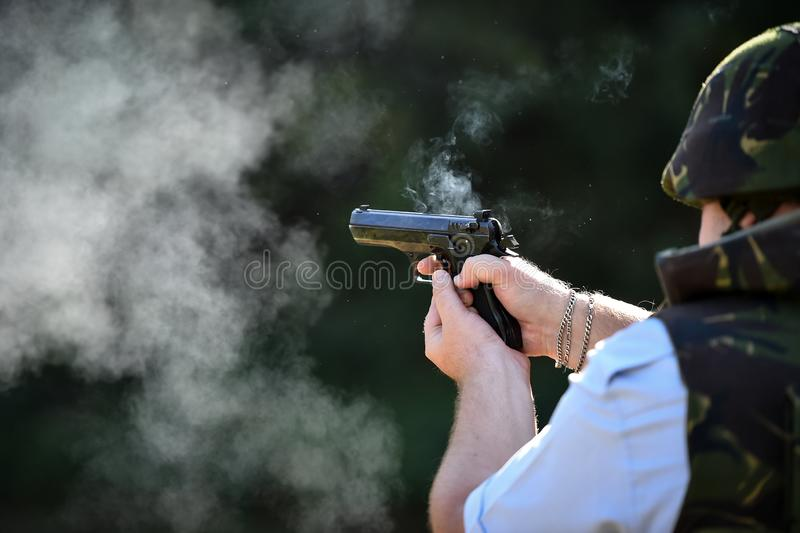 Utomhus- skytte med en 9mm pistol i en skjutbana royaltyfria bilder